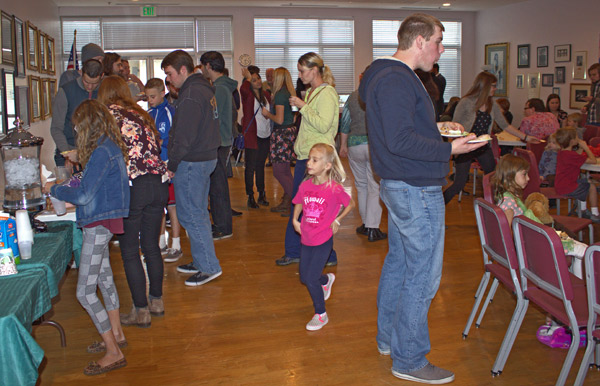 Members of the Logan Community of Good mingle after services at the Dasante Theatre on Sunday (Morgan Pratt photo)